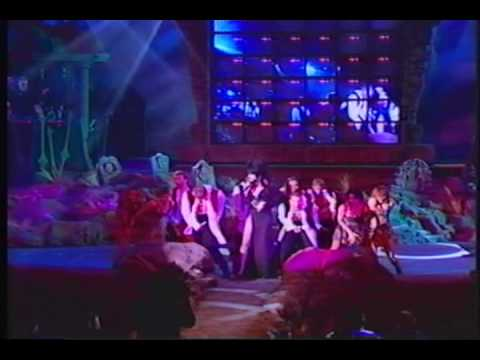 (New) Elvira performing haunted house live on stage.